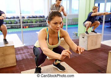 woman doing box jumps at group training in gym