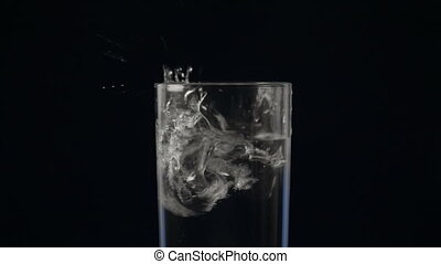 Glass of water and falling ice cube, closeup video