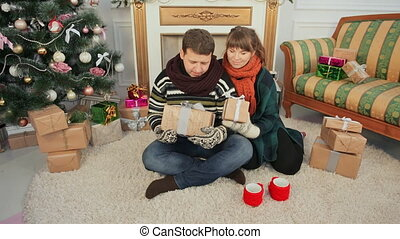 A young young couple gives presents to the camera for the viewer. Christmas and New Year theme.