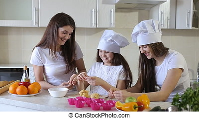 young beautiful mother teaches her daughters the secrets of culinary art. happy family in the kitchen