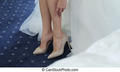 Bride puts on wedding shoes and shows her beautiful legs