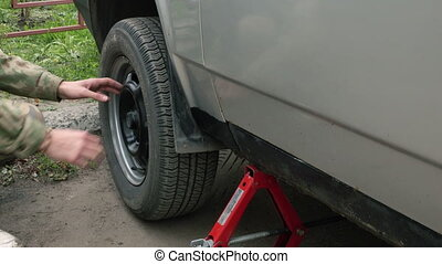 man changing a wheel on a car. - Men removes a wheel from...