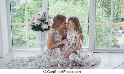 mother and daughter sitting in front of a big window