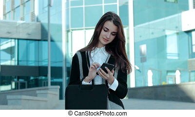 pretty young girl makes a text massage on mobile phone