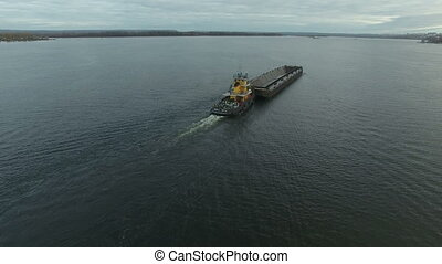 Empty barge is moving up the Volga river early in the...