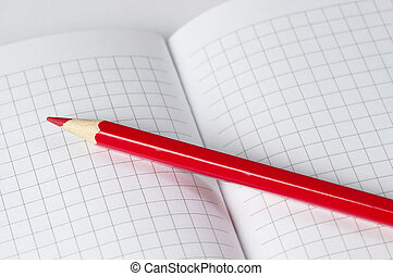 Red pencil macro shot over checked paper