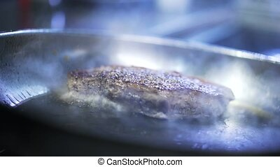 Close up of a beef steak being fried in a pan