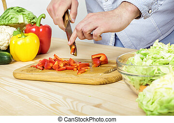 Hands of man chopped red bell pepper for salad on board,...