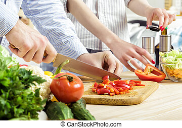 Hands of man chopped red bell pepper on board. Couple...