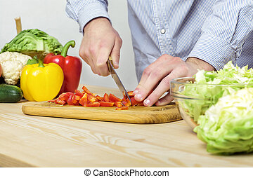 Hands of man chopped red bell pepper for salad on board, close-up