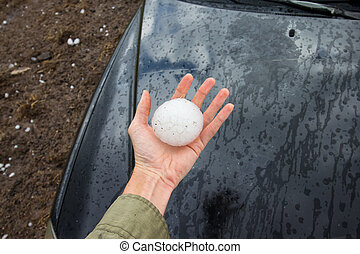 Storm chaser holds a baseball sized hailstone dropped by a...