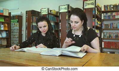 Two students studying books at library