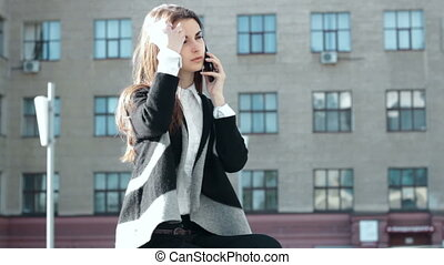 Cutie girl drinks coffee and talks on mobile phone in the...