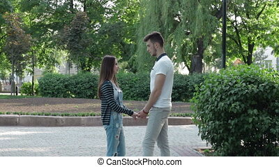 beautiful couple holding hands in the Park and talk
