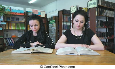 Two beautiful students sitting at library