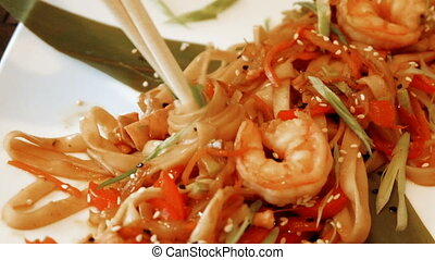 Woman eating Chinese noodles using chopsticks - Woman eating...