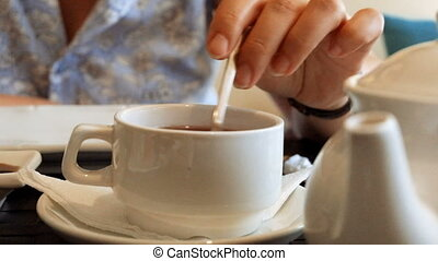 Woman Mixing sugar in a cup of tea Close-Up.