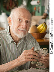 Senior man at home counting money