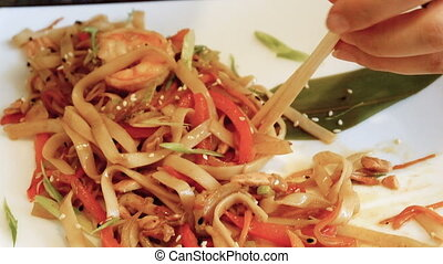 Woman eating Chinese noodles with fryed vegetables using...