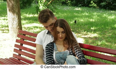 young pretty couple hugs and talks on a bench