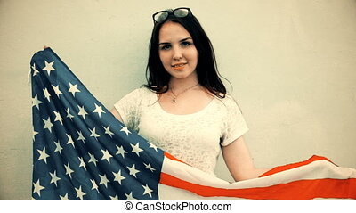 Young latino woman holds american flag in front of her body...