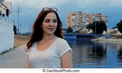 Portrait of cute red hair woman posing by the river side...