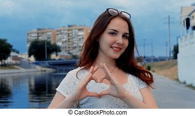 Ginger hair girl make Hand heart sign by her fingers,...