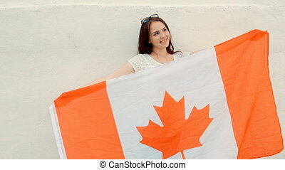 Young latino woman holds Canada flag in front of her body...