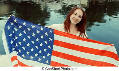 US Independence Day, the fourth of July. Beautiful young girl in casual style smiling with American flag in her hands. Ginger hair, water on background