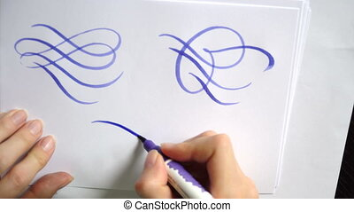 Beautiful calligraphic curls with a brush on sheet of paper