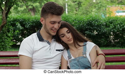 handsome guy with a girl sitting on a bench outdoors