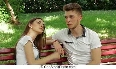 woman speaks and laughs with a guy on a bench outdoors -...