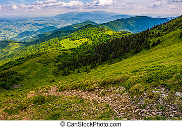 footpath down the hill through forest on mountain ridge -...