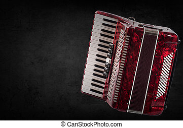 Red accordion on wooden grey background. Write text.