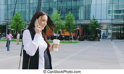Elegant business woman walking and talking on a phone during a coffee break
