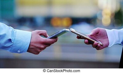 Closeup of two hands using mobile phones with a great cityscape at the background