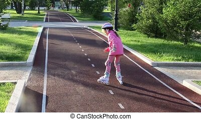 A seven-year-old girl learns rollerblading in a summer park...