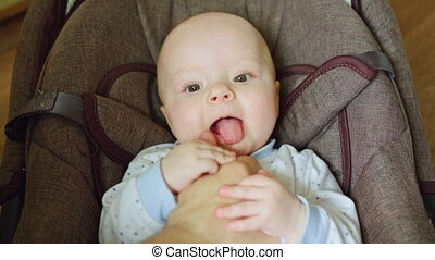 Baby Lying in a Pram Tickled by Father's Hand