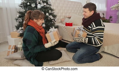 Young couple admire Christmas presents and give the viewer....