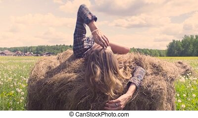 Young woman laying on haystack at summer - Happy young woman...
