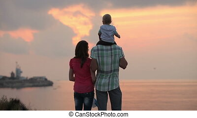 Family with child watching the sunset at the sea, there are...