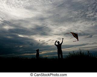 man and little boy flying a kite at sunset - father and son...