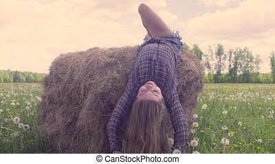 Young woman falling down from haystack - Happy young woman...