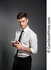 Businessman in formalwear holding mobile phone and looking at camera