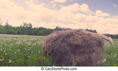 Young woman running and jumping on the haystack - Happy...
