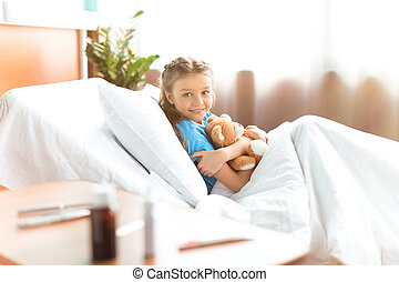 Cute little girl lying in hospital bed with teddy bear and...