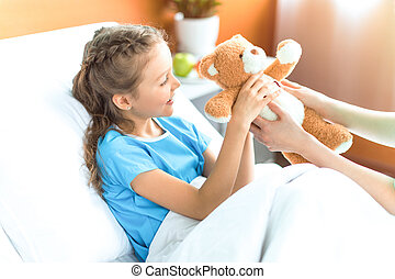 Cropped shot of nurse giving teddy bear to smiling little girl in hospital
