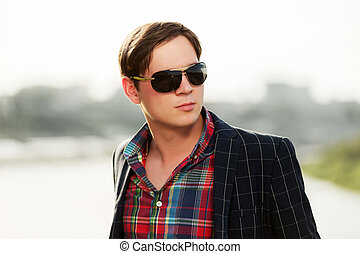 Portrait of young fashion man in sunglasses outdoor