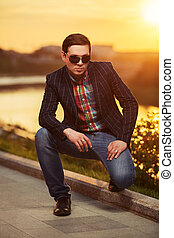 Portrait of young fashion man in sunglasses at sunset