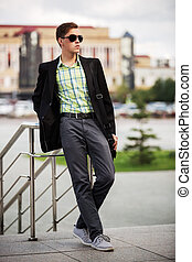 Young fashion man in sunglasses on the city street